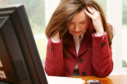 Woman with head in her hands at a computer desk.