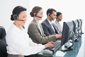 Business people with headsets using computers in office.